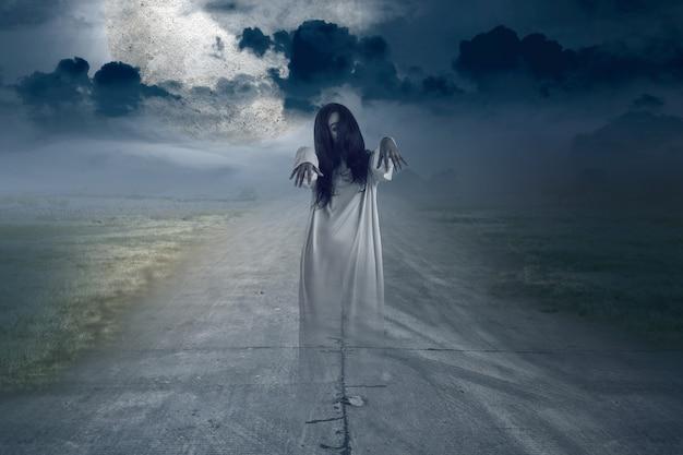 Страшная женщина-призрак, стоящая с фоном ночной сцены. концепция хэллоуина