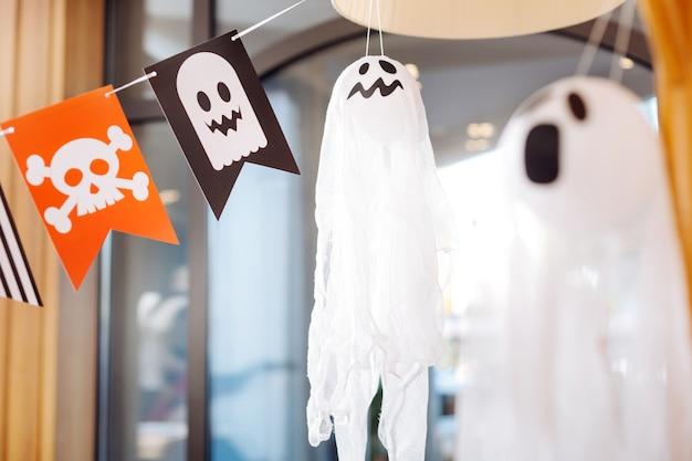 怖い幽霊。ハロウィーンの子供たちのパーティーの装飾として横たわっている頭蓋骨と怖い幽霊と旗