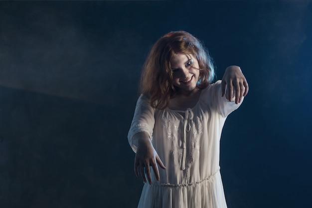 Scary girl in white dress from horror film on dark