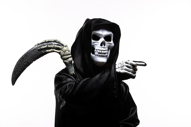 Scary grim reaper in black clothes with scythe pointing out on white