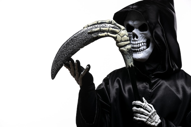 Scary grim reaper in black clothes with scythe on white