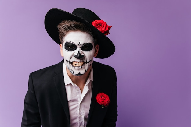 분노를 표현하는 좀비 복장의 무서운 남자. 할로윈 파티 동안 장난하는 muertos 의상에서 남자의 스튜디오 사진.