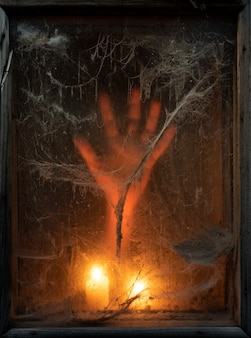 Scary halloween background with creepy cobwebs and hand in the dark