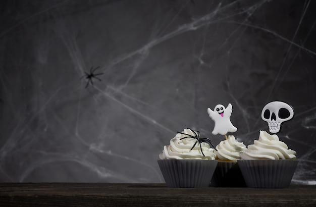 거미줄과 어두운 배경에 무서운 할로윈 컵 케이크.