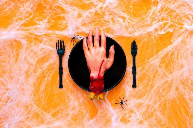 Страшная концепция званого обеда на хэллоуин с поддельной режущей рукой на черной тарелке, ноже и вилке с пауком и паутиной на оранжевом фоне.