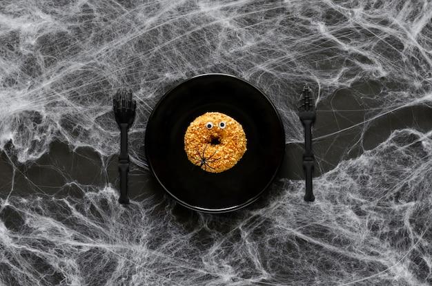검은 접시에 재미있는 도넛 얼굴이 있는 무서운 할로윈 저녁 파티 개념, 검은 배경에 거미와 거미줄이 있는 나이프, 포크.