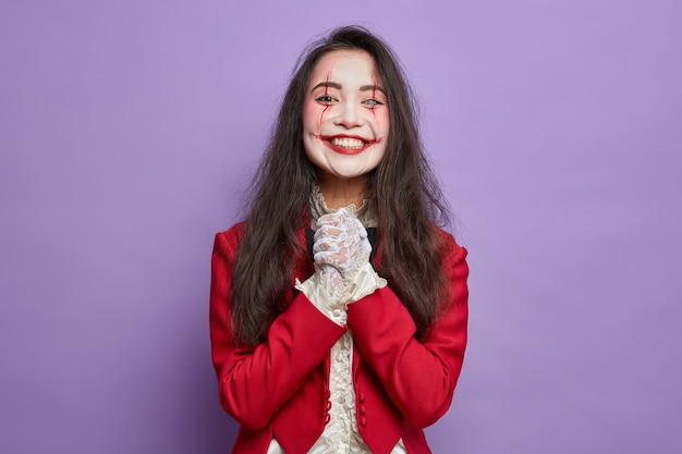 Scary halloween girl with spooky makeup smiles gladfully anticipates for masquerade party keeps hands together isolated on purple wall. bloody face art