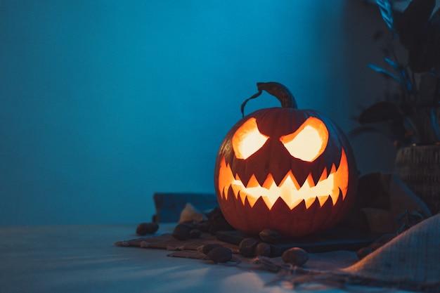 Страшная тыква на хэллоуин темный фон с разноцветными огнями тема хэллоуина страшная открытка