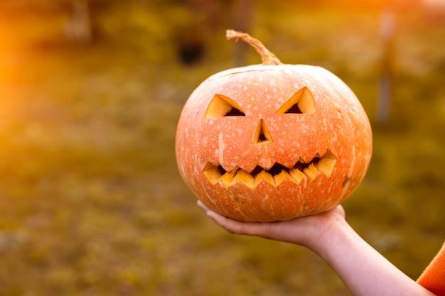 Страшная тыква на хэллоуин в руке