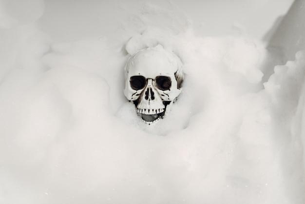 Scary human skeleton lying in the bathtub, humor