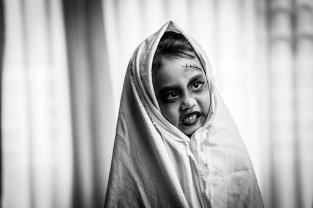 Scary little girl in hallo ween costume standing indoor