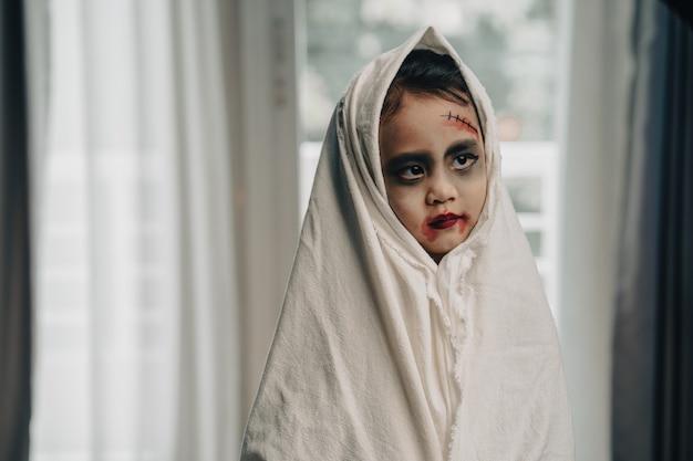 Scary little girl in halloween costume standing indoor
