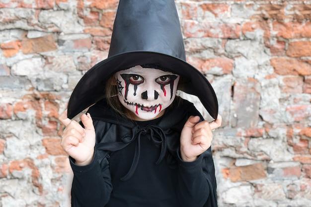 Страшная маленькая девочка в костюме ведьмы улыбается