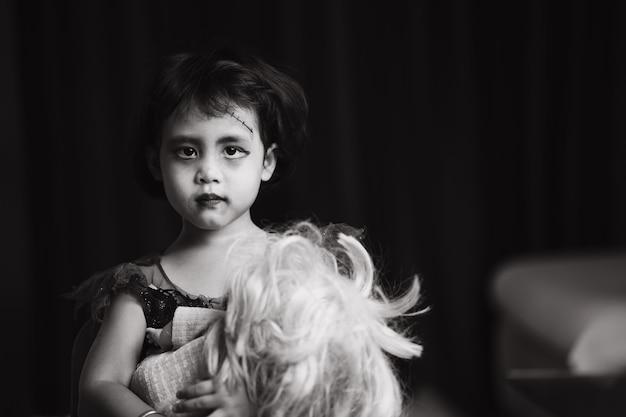 Scary looking small girl in halloween costume standing indoor