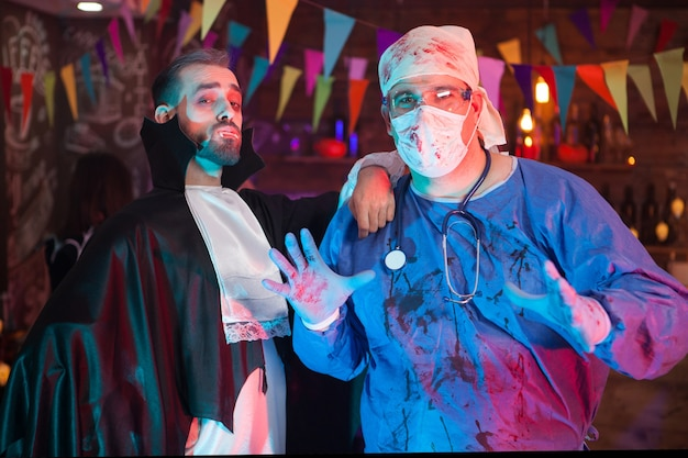 Scary man in a doctor costume covered in blood with his handsome dracula friend celebrating halloween. halloween costumes.
