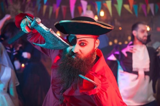 怖い男はハロウィーンのお祝いで斧を持っているパーティーのようにドレスアップしました。バックグラウンドで魔女のような格好をした女性。