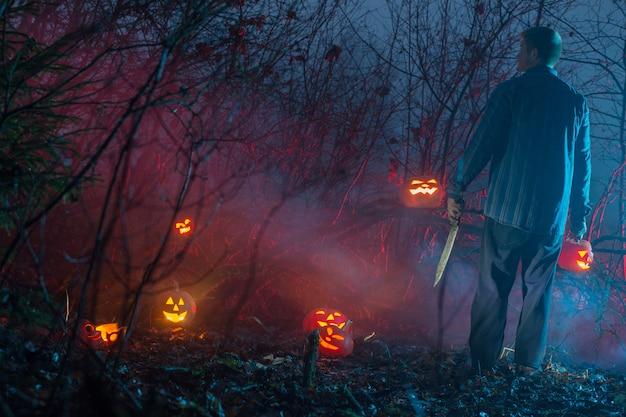 夜の森の怖い男がハロウィンのカボチャを切っています