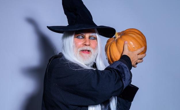 호박과 마녀 모자에 무서운 남자입니다. 잭 오 랜턴을 가진 악마. 해피 할로윈. 휴일 의상에서 잘생긴 남자입니다.