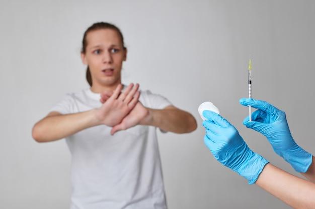 Страшный человек отказывается от вакцинации против коронавируса, от вакцинации против covid-19. рука врача с инъекцией вакцины