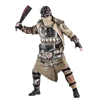 Страшный постапокалиптический выживший в бронированной одежде ручной работы, вооруженный мачете, опасное существо с лицом, спрятанным за маской и очками, в лохмотьях, стоящее с холодным оружием в руках студия съемки