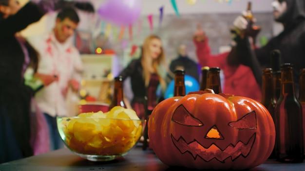 Страшная тыква на вечеринке, в то время как группа людей танцует на фоне празднования хэллоуина