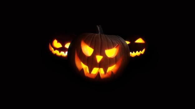 무서운 호박은 밤에 빛납니다. 검정색 배경에 할로윈 사진입니다. 공포와 휴일 개념