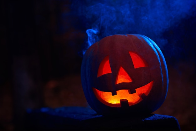 Scary red pumpkin with fire inside and big eyes