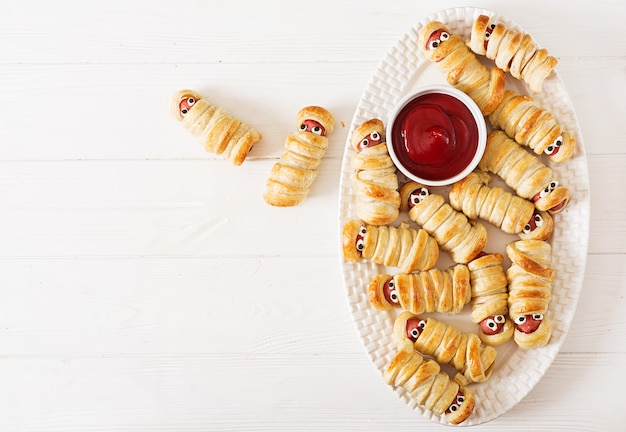Scary sausage mummies in dough with funny eyes on tablе. halloween food.