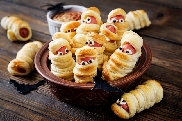Scary sausage mummies in dough with funny eyes on table. funny decoration. halloween food.