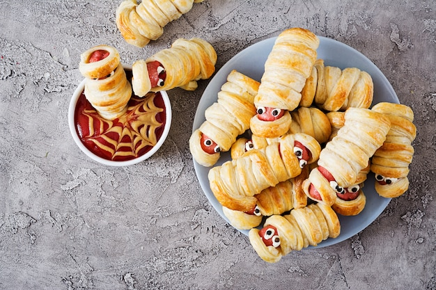 Scary sausage mummies in dough with funny eyes on table. halloween food.