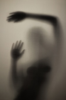 Scary silhouette of a girl behind a glass in the bathroom in the light