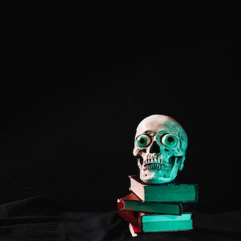 Cranio spaventoso con occhi di fantasia che si trova sulla pila di libri
