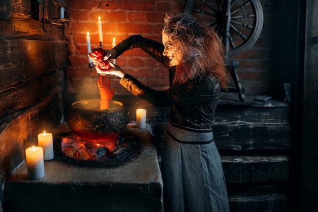 Scary witch cooking soup with human body parts, dark powers of witchcraft, spiritual seance with candles.