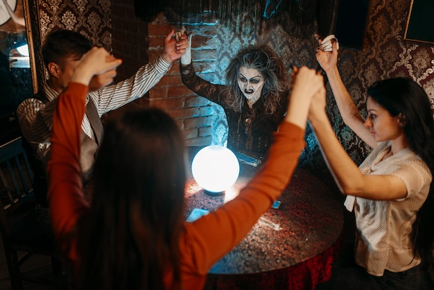 Страшная ведьма читает магическое заклинание над хрустальным шаром, молодые люди поднимают руки на духовном сеансе. женщина-предсказательница вызывает духов