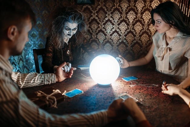 Scary witch reads a magic spell over a crystal ball, young man and woman on spiritual seance.