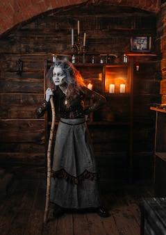 怖い魔女が杖に寄りかかって立っている、交霊会