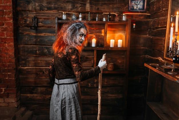 杖を持った怖い魔女、背面図。黒魔術の精神的な交霊会。女性の占い師が精霊を呼ぶ、ひどい占い師