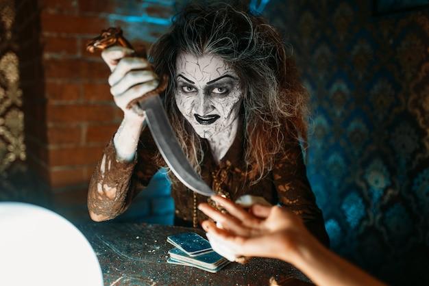 Страшная ведьма с ножом читает магическое заклинание над хрустальным шаром, молодые люди на духовном сеансе. женщина-предсказательница вызывает духов