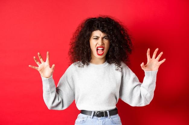 Donna spaventosa che cerca di spaventarti, gridando e mostrando il gesto degli artigli di animali, urlando a persona, in piedi su sfondo rosso.