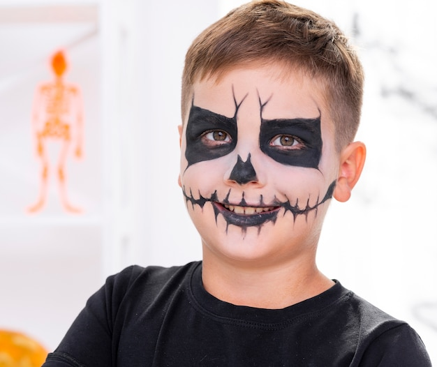 Scary young boy with face painted for halloween