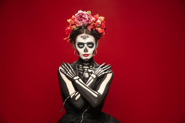 怖い。サンタムエルテ聖人の死や明るいメイクのシュガースカルのような若い女の子。コピースペースで赤いスタジオの背景に分離された肖像画。ハロウィーンや死者の日を祝う。