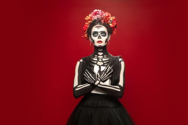 Страшная молодая девушка, как смерть санта-муэрте, святой или сахарный череп с ярким макияжем