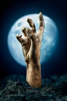 Mano di zombi spaventosa da terra di notte