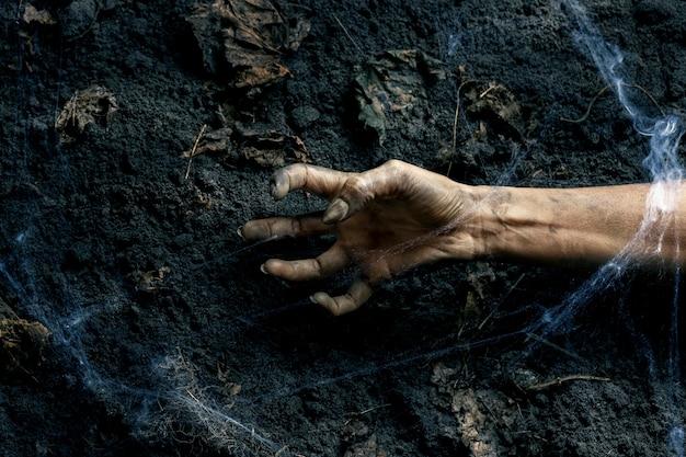 Страшная рука зомби на земле