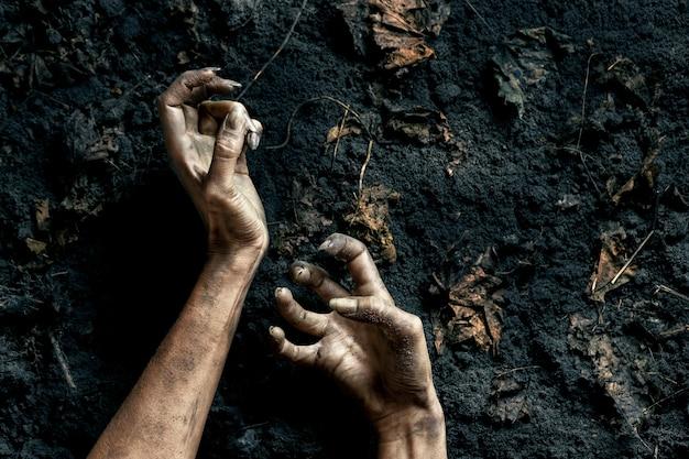 Страшные руки зомби на земле