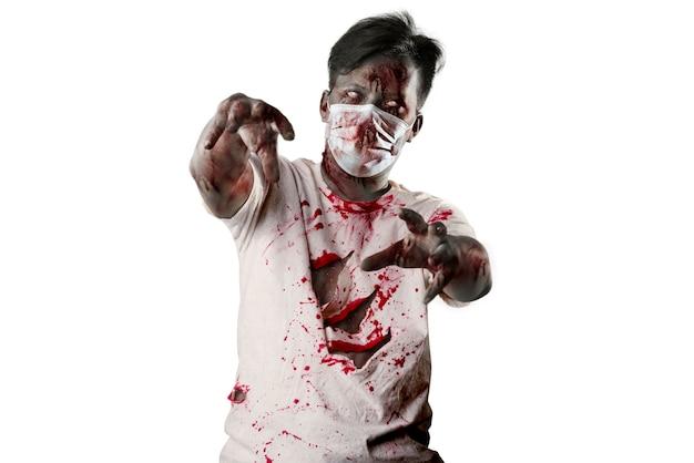 白い背景の上に孤立して立っている彼の体に血と傷を持つフェイスマスクの怖いゾンビ