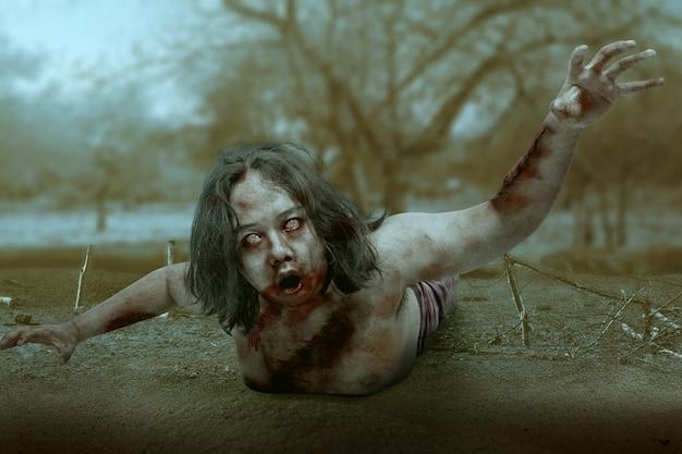 피와 상처를 입은 무서운 좀비가 현장에서 기어 다니는 몸에