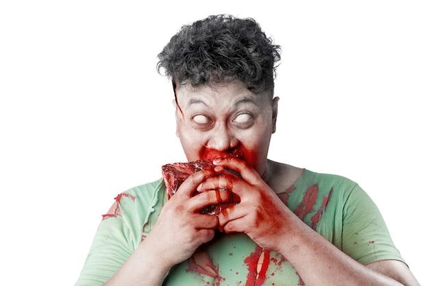 彼の体に血と傷を持つ怖いゾンビは、白い背景の上に分離された生肉を食べる