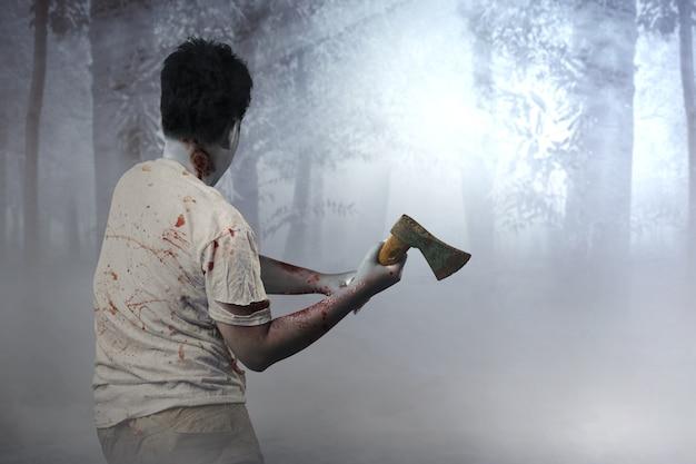 안개가 자욱한 배경에 도끼를 들고 몸에 피와 상처가 있는 무서운 좀비