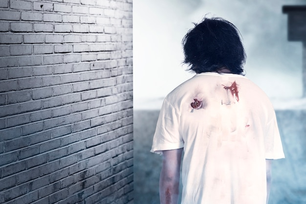 버려진 건물에 서있는 그의 몸에 피와 상처가있는 무서운 좀비